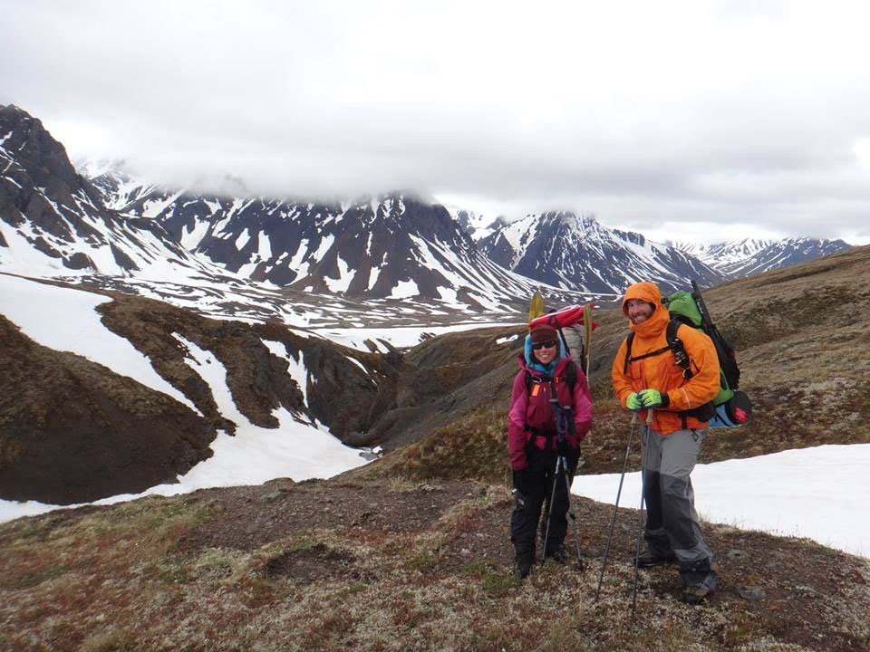 Two people with large packs hiking in snowy mountains