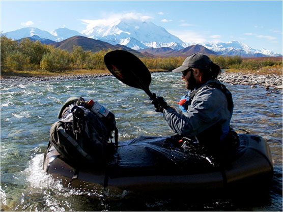 person in a packraft floating on a river, large white mountain in the distance