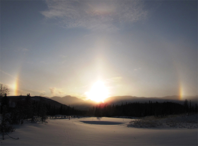 image of a sundog - bright flares reflect points of light far to the right and left of the sun