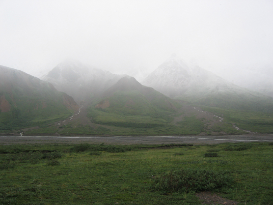 a green plain with mountains in the distance mostly shrouded in gray mist and rain