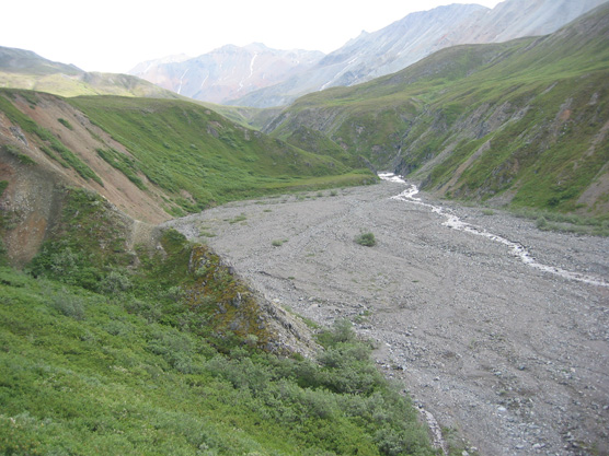 a river cutting a narrow, deep divide between two small ridges