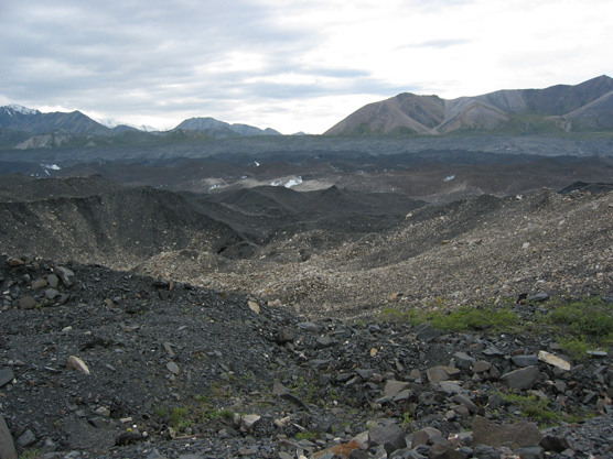 a rough, rocky landscape, with mountains in the distance