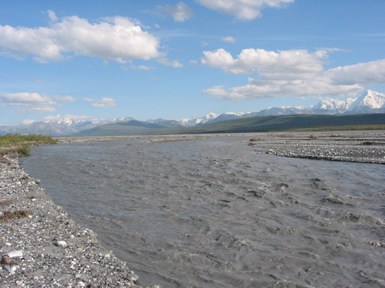 a wide, dark gray river, snow-capped mountains in the distance