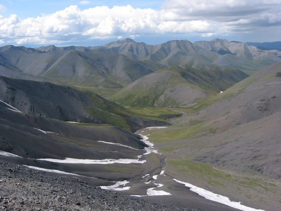 a rocky, snow-dotted slope leading down to a creek, mountains in the distance