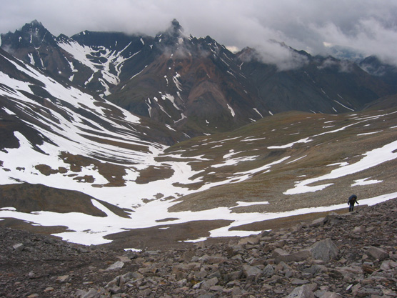 mountains covered at the top by thick clouds, with patches of snow and a person, dwarfed in the scenery, hiking among rocks