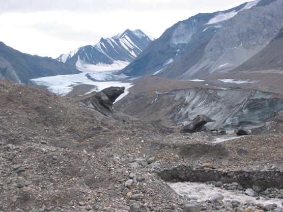 a rocky, uneven landscape leading up to a small glacier and steep, snow-dotted mountains