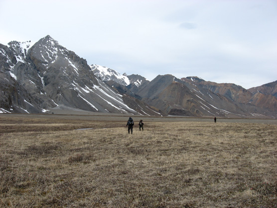 three people hiking across a wide, brown plain in front of distant, snow-dotted mountains