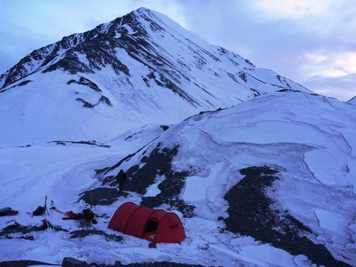 a red tent staked out on a snowy mountainside