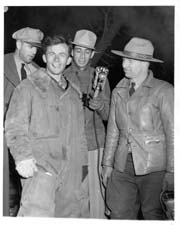 George Hopkins (left foreground) with park superintendent (right) and reporters (background)
