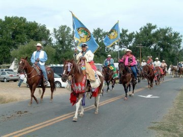 A procession of people on horseback going down a road.