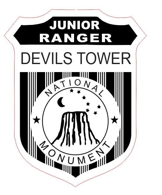 black and white Devils Tower Junior Ranger badge with sketch of the Tower with moon and stars above it