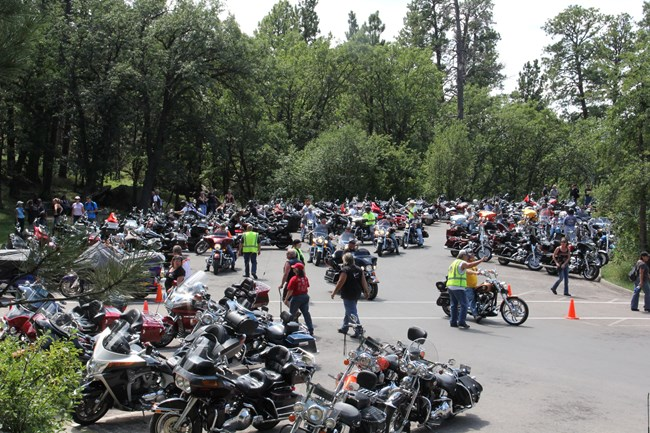 parked motorcycles fill the parking lots with people crowded throughout; volunteers direct motorists where to park