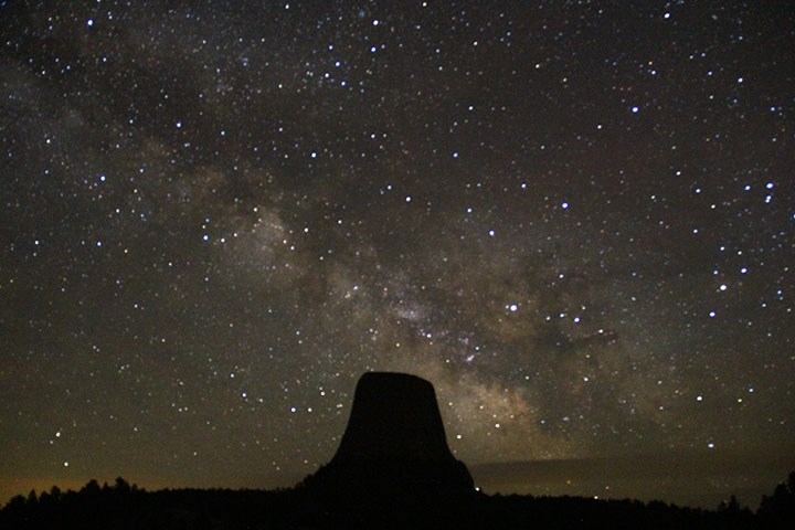 A night sky photo of Devils Tower with the Milky Way in the sky