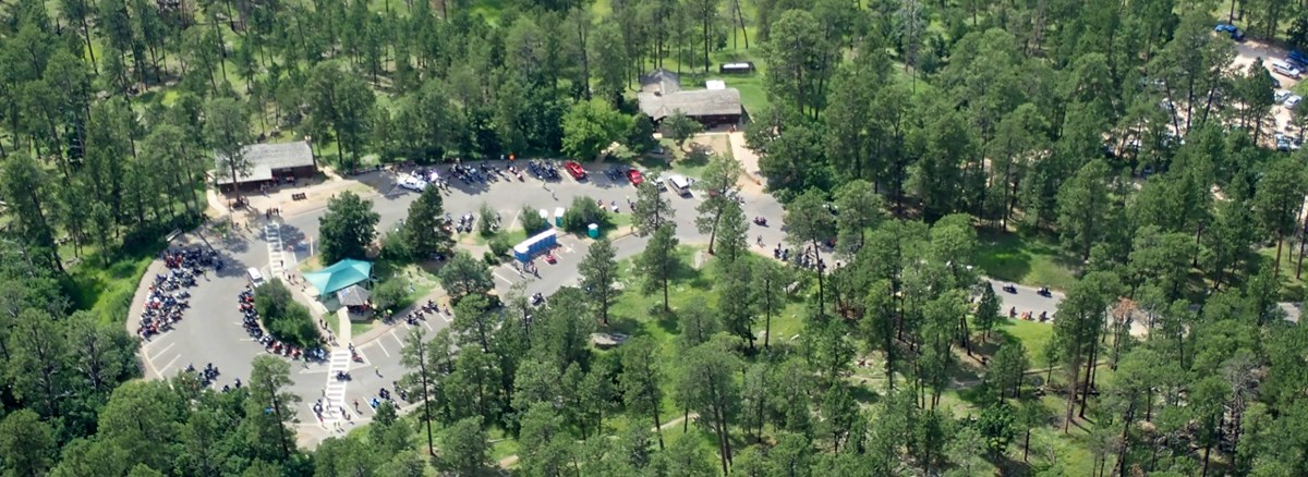 aerial view of visitor center parking lot with cars and people