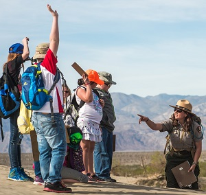 Kneeling on the sand dunes, a ranger points towards students raising their hands.