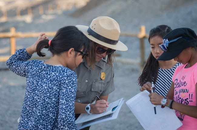 A park ranger writes on a Junior Ranger book with three young people.