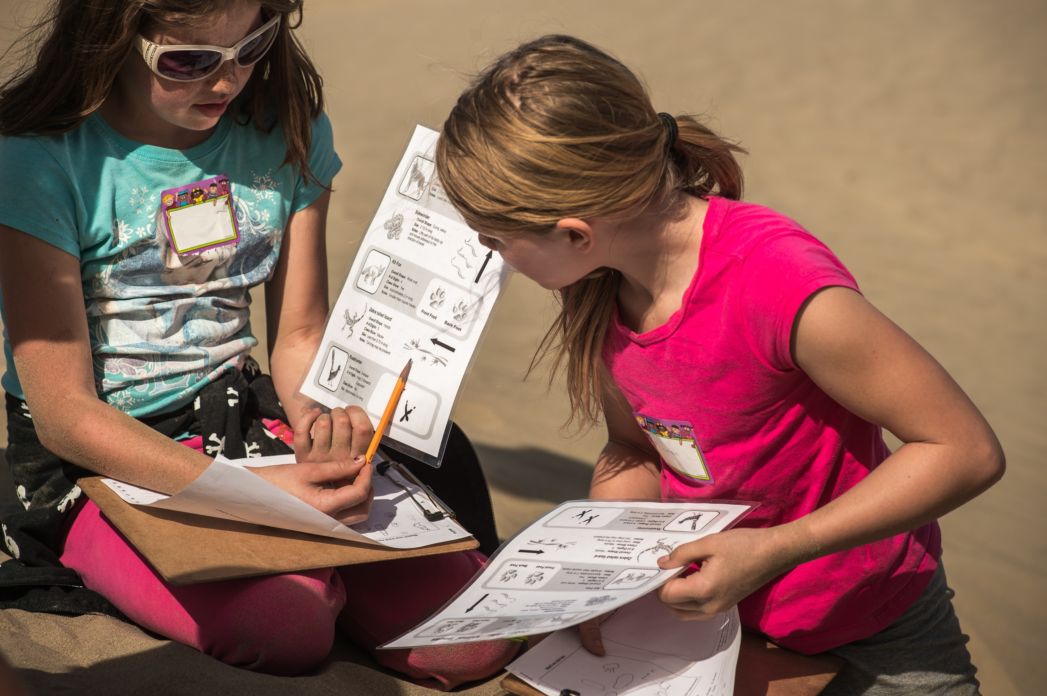 Two students look at an animal tracking field guide.