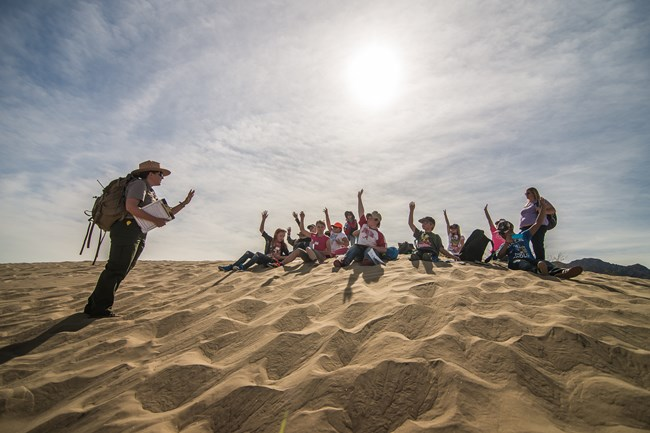 Students sit in front of a ranger on the sand dunes.