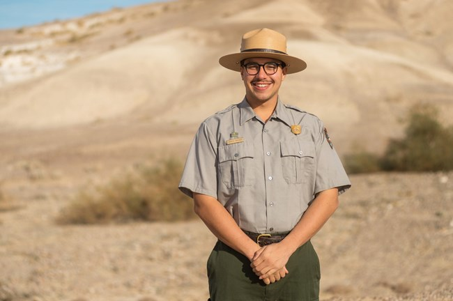 A ranger with a flat hat stands in front of a tan hill facing forward.