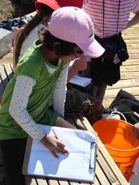 A student writes on a clipboard while looking into a bucket.