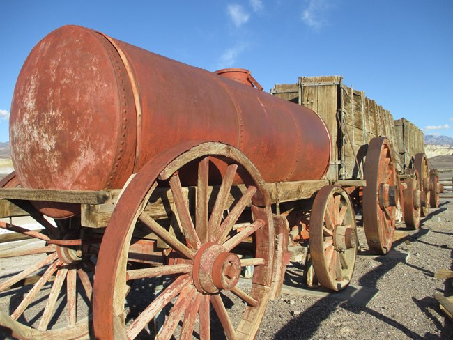 A large rusty tank on large wooden wagon wheels with two large wooden carts behind it.