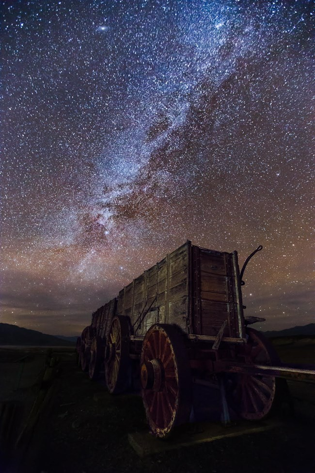 At night, a wooden wagon with large spoke wheels is seen from the front with the milky way and stars above.