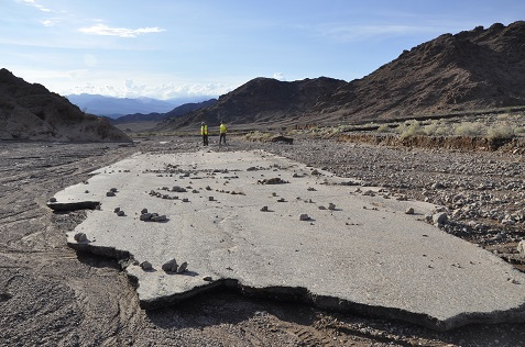 Two NPS employees walk on a damaged section of road after October's flood.