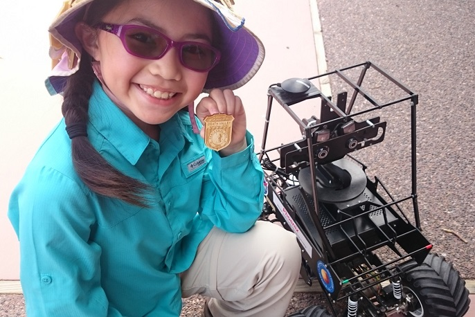 A child next to a mini Mars rover proudly shows her Junior Ranger badge