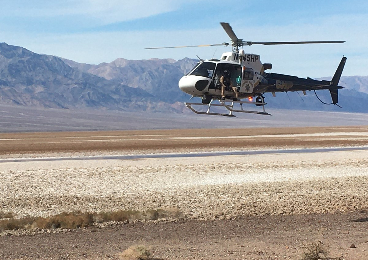 A helicopter is in the foreground in top right corner of photo. It is about 20 feet off the ground, which is gravel in foreground and salt in midground. Mountains are in background.