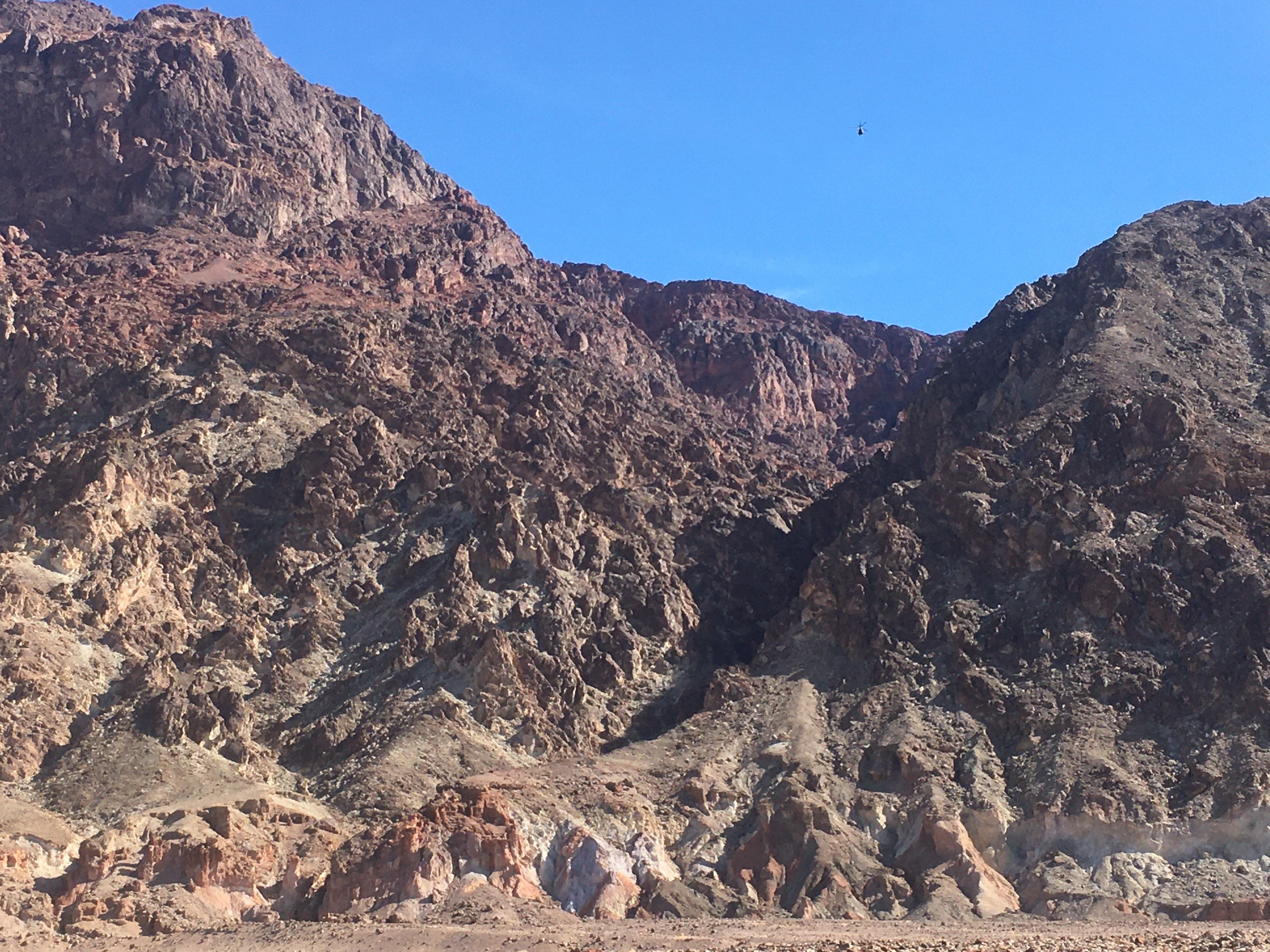A helicopter is a small speck against blue sky over the dark brown canyon, as viewed from Badwater Road.