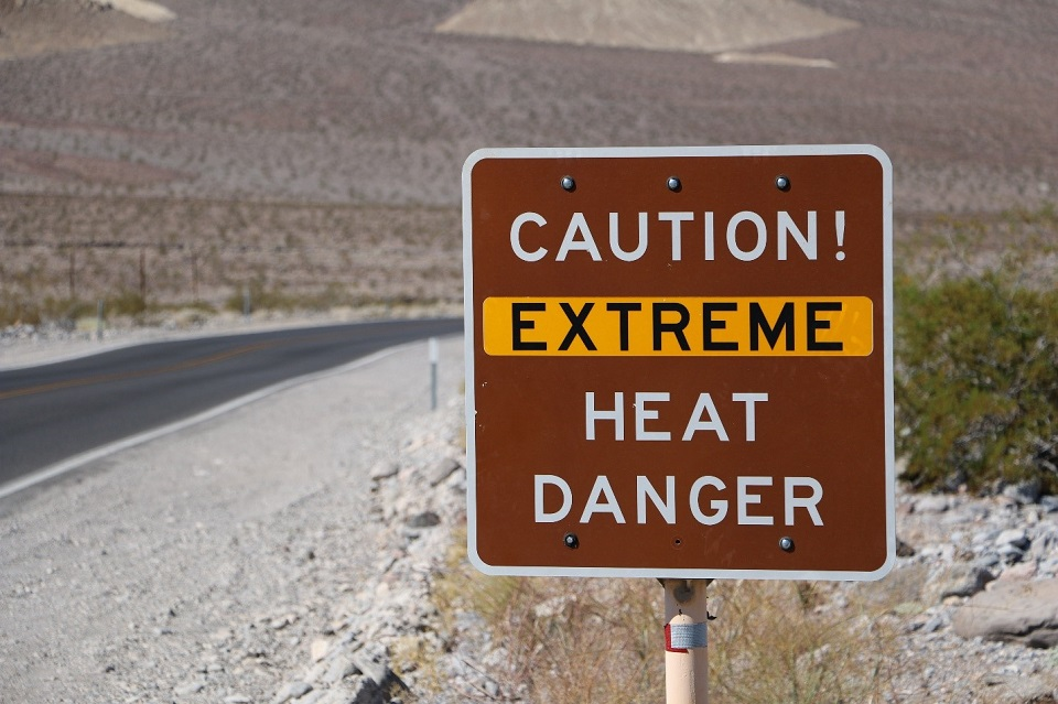 "A brown sign reading ""Caution! Extreme heat danger"" is shown to the right of a paved road in Death Valley National Park."