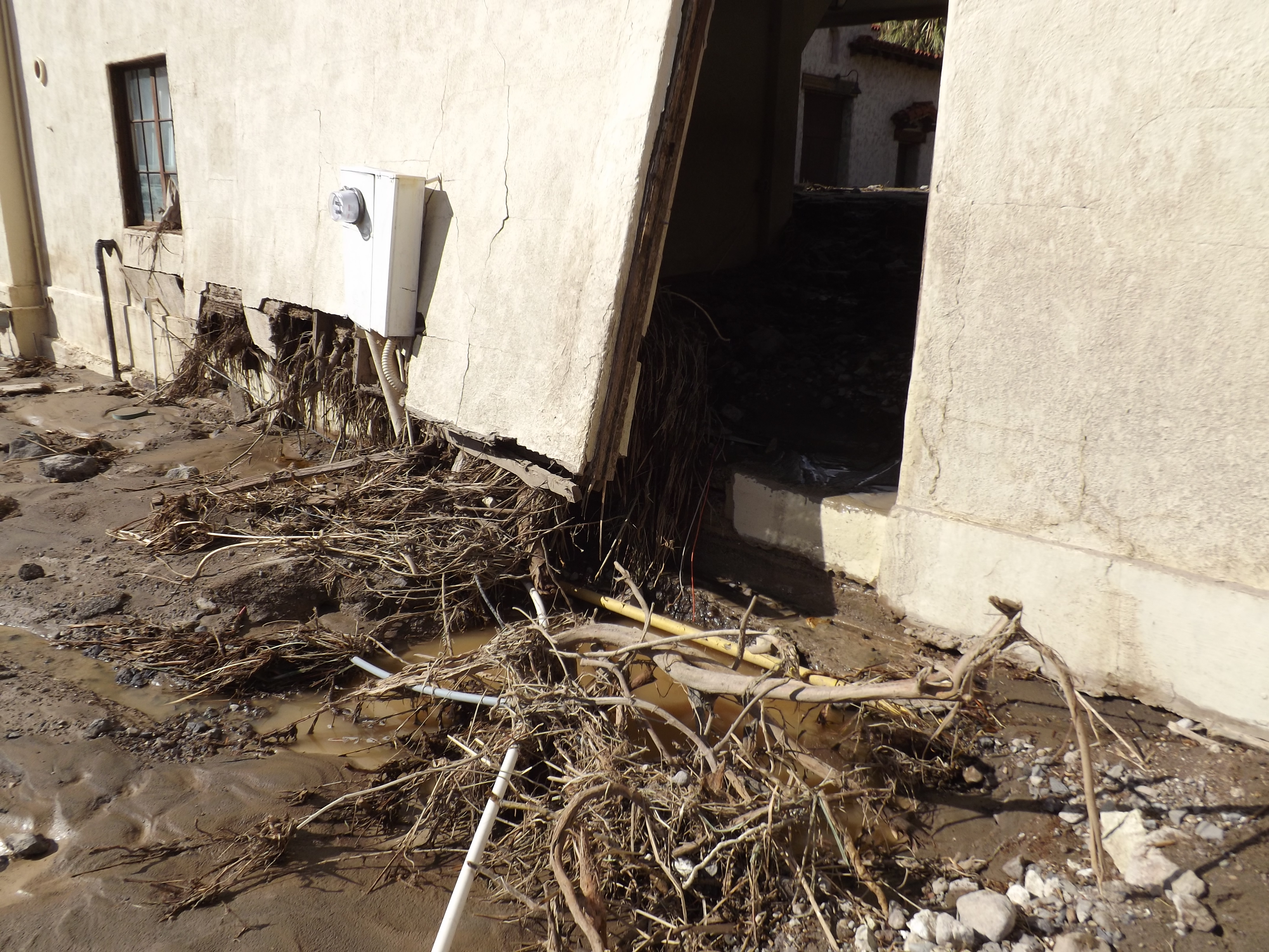 Rocks, soil and other flood debris litters the front of a long, damaged building.