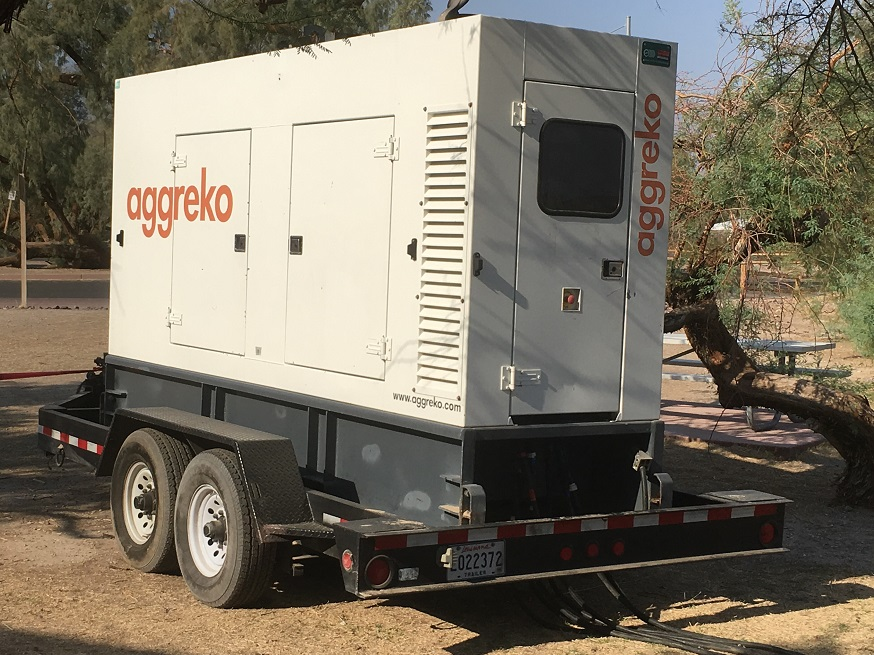A white trailer-mounted generator is hooked by thick cables to an electrical panel behind Furnace Creek Visitor Center.