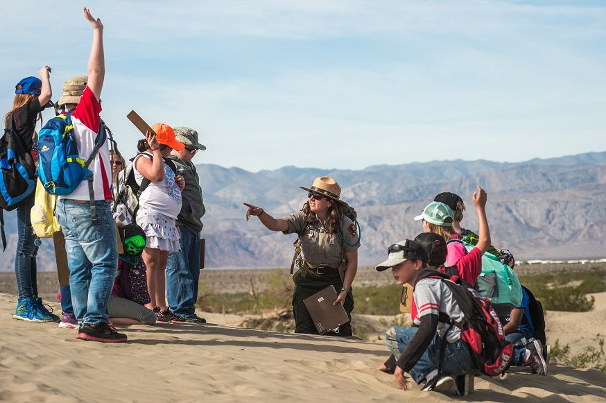 A park ranger kneels in sand while 4th grade students raise their hands to answer a question