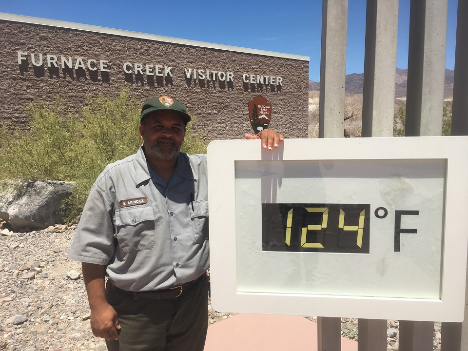 Park ranger Roberto Mendez stands next to the temperature reading 124 degrees Farenheit. Furnace Creek Visitor Center and the National Park Service arrowhead can be seen in the background.
