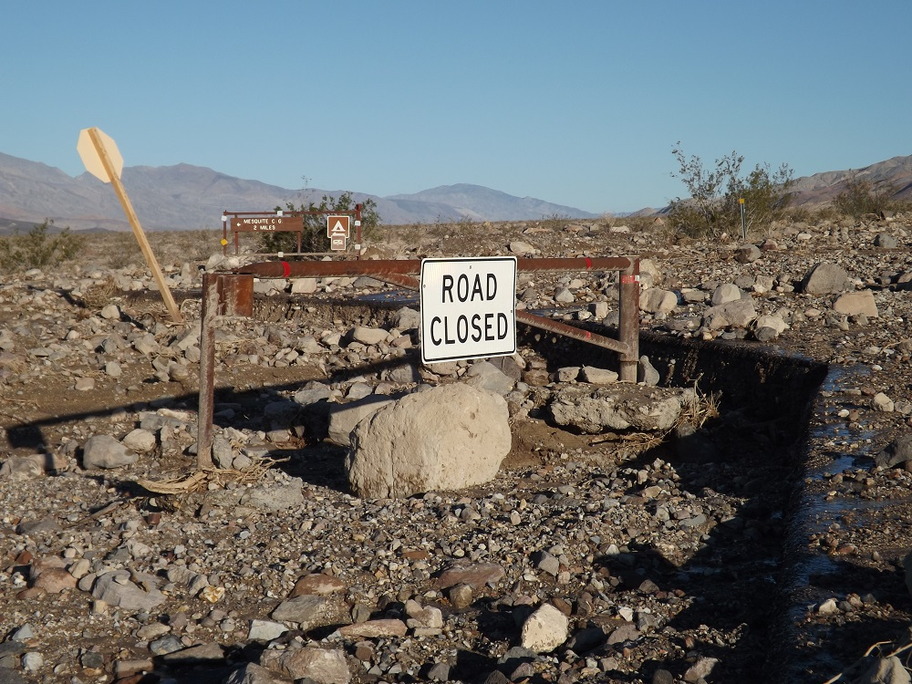 "a ""road closed"" sign on a barricade among mud, rocks, and other flood debris"