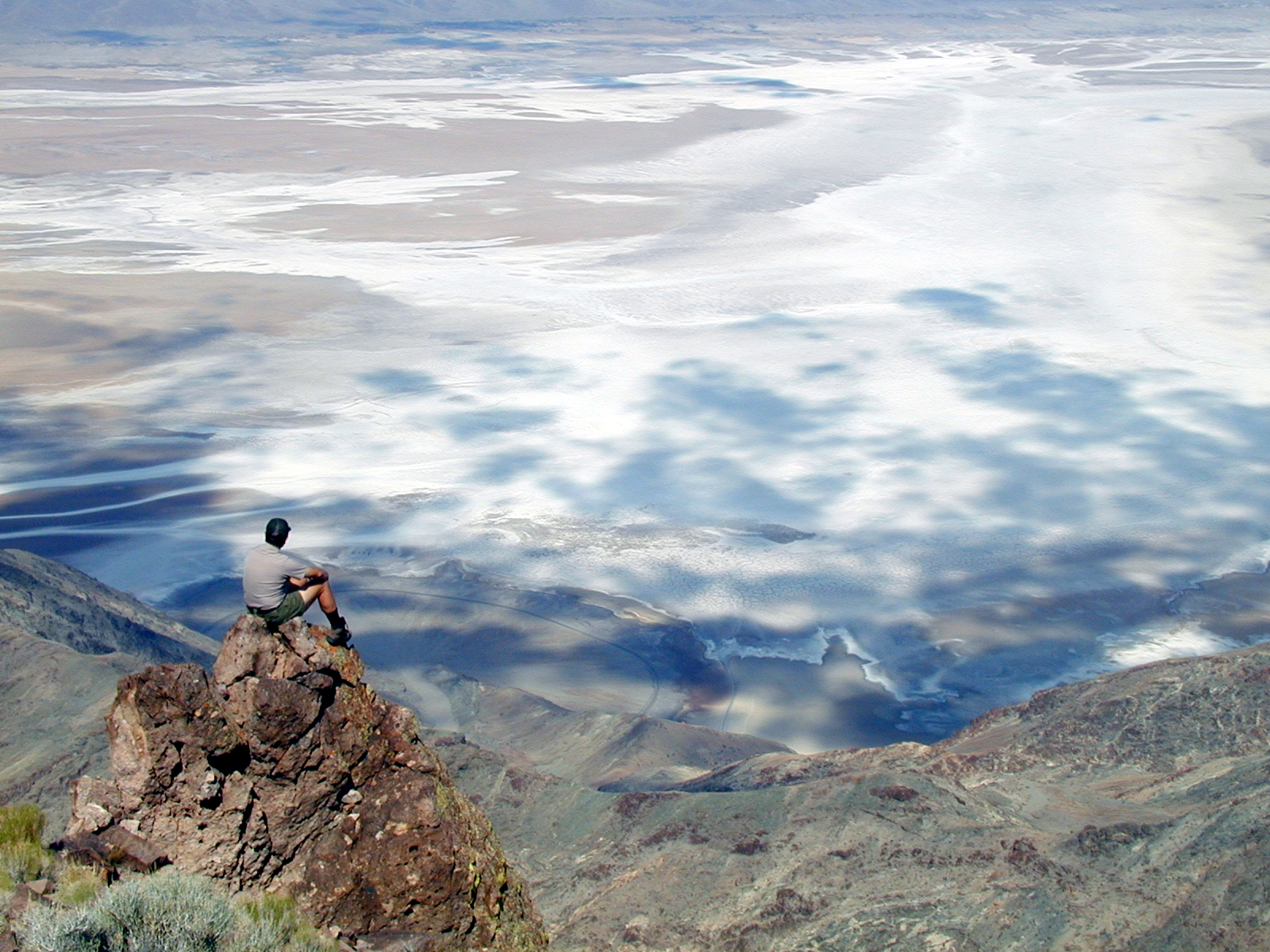 A park ranger sits on a rocky outcropping looking down on the white, flat salt flats.