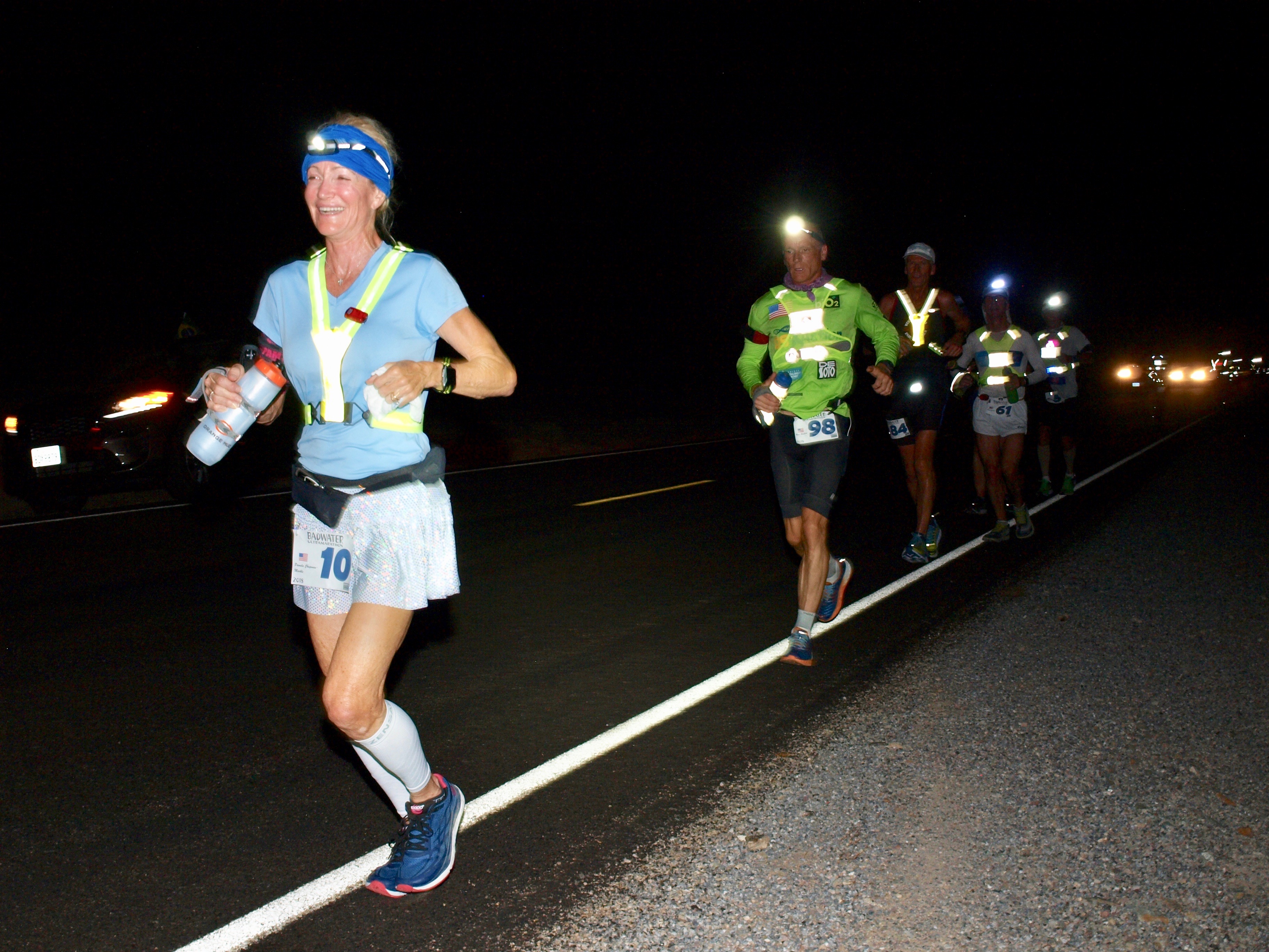 Runners, at night, in a string, run along a paved road.
