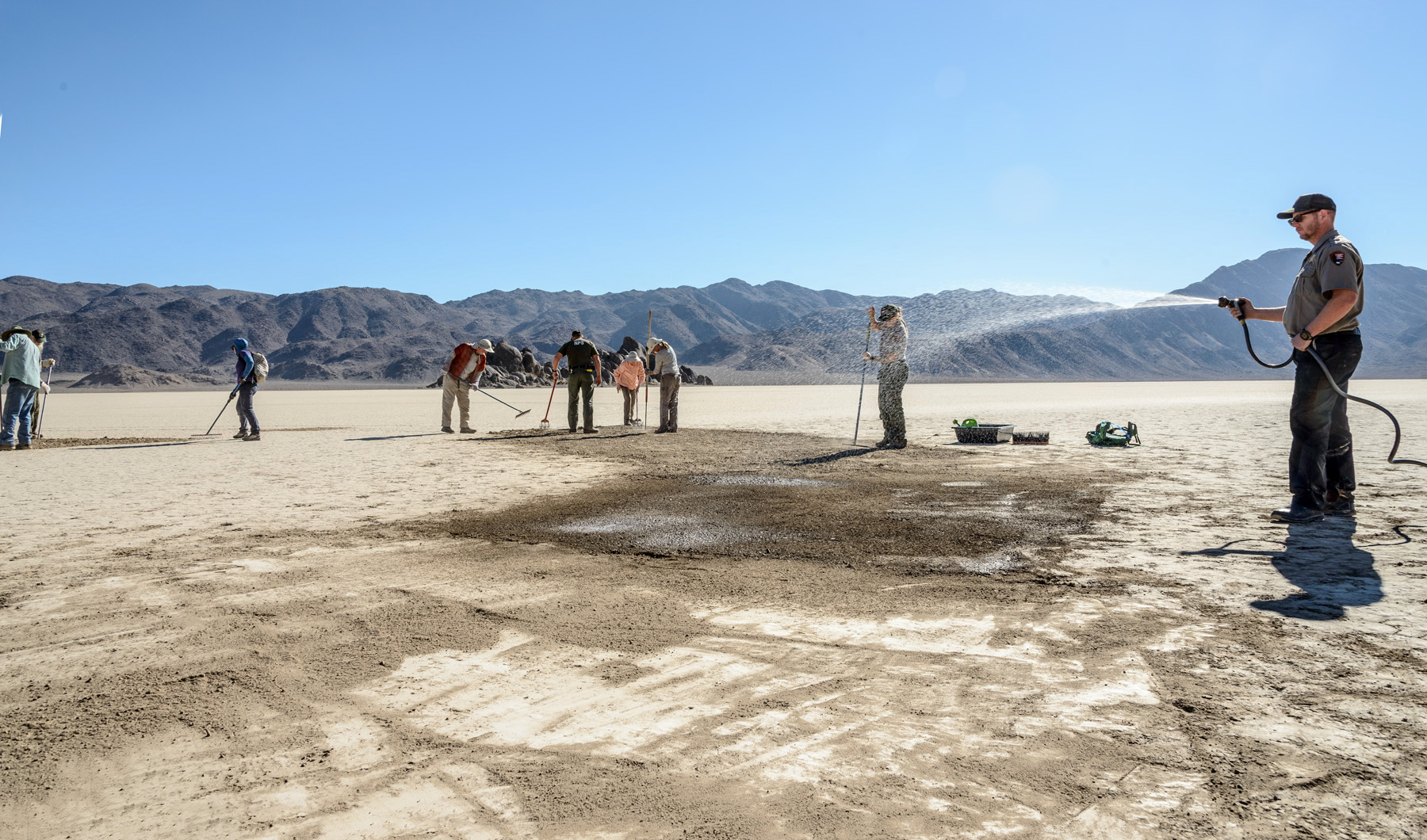 A group of people are raking and watering a large flat playa, where road tracks had been left in the dirt.