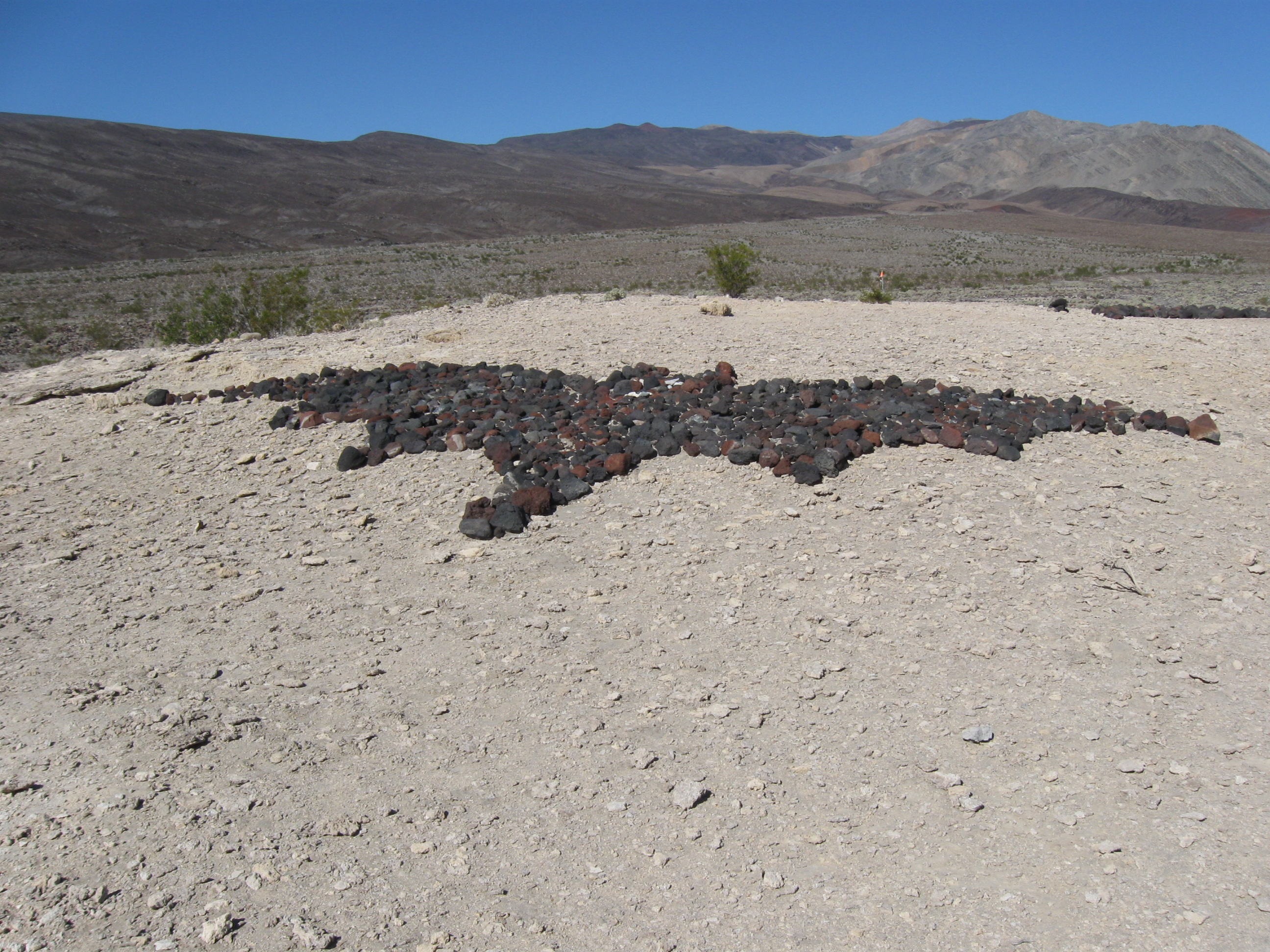 Dark rocks have been placed in the shape of a flying bat on the ground near Saline Valley Warm Springs.