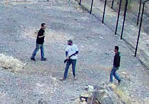 Grainy still image from security camera shows three men inside the fence at Devils Hole.