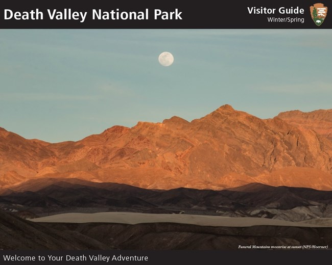 A moon rises above golden-colored desert mountains.