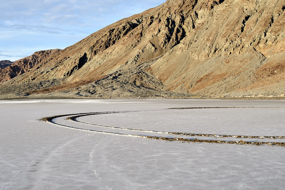 A semicircular pattern of vehicle tracks filled with water contrasts with the white salt