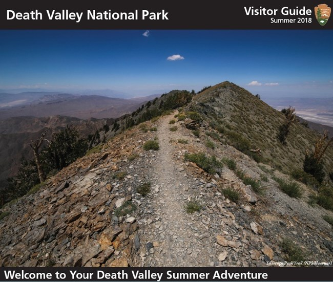 A rocky ridge line trail on a desert mountain, on the cover of the summer visitor guide.