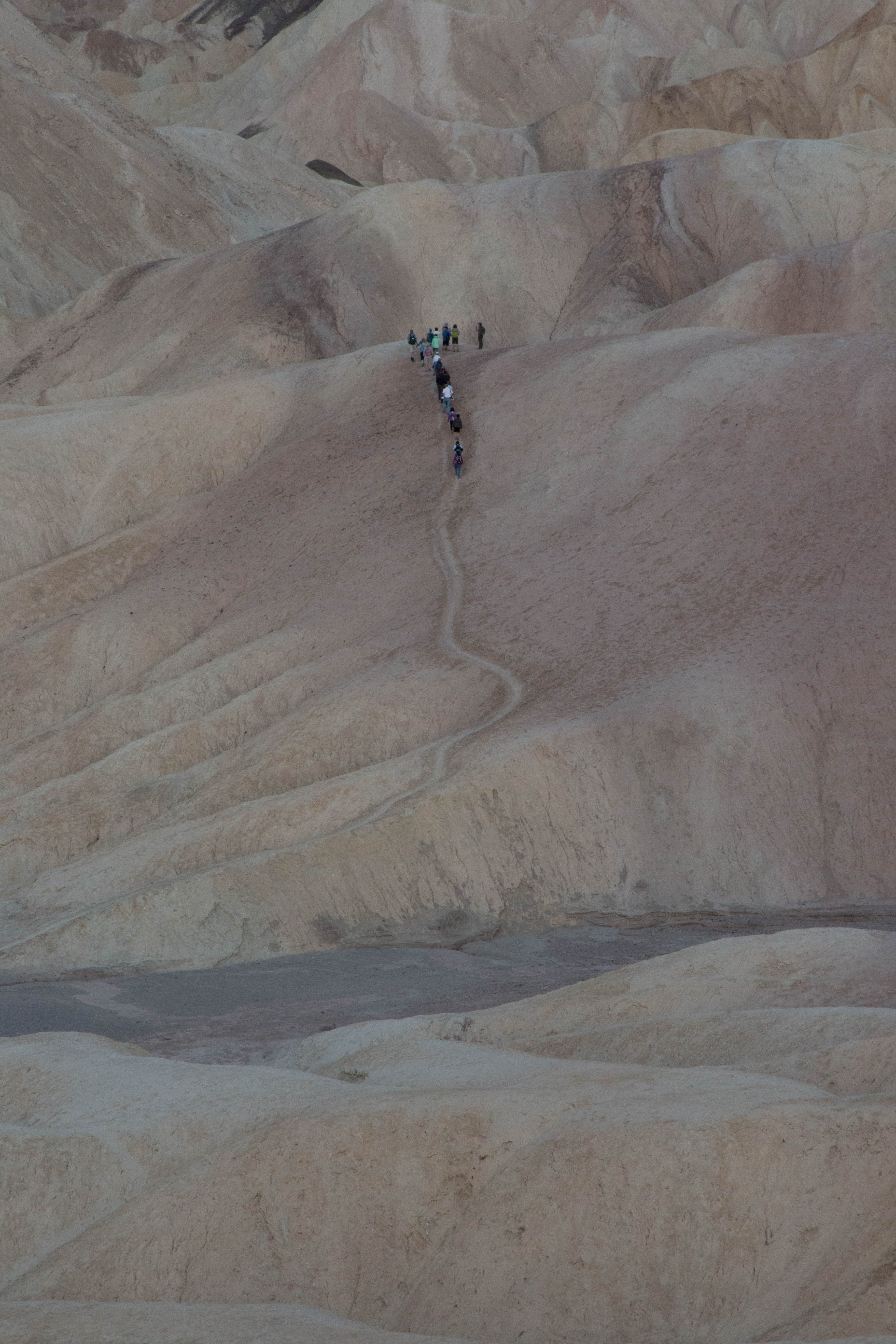 A group of hikers travel up a path through highly eroded desert hills.