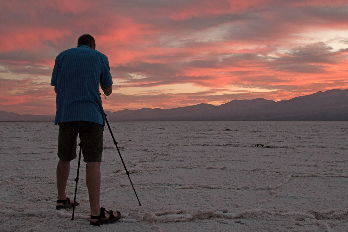 A photographer stands with a tripod on a vast salt flat.