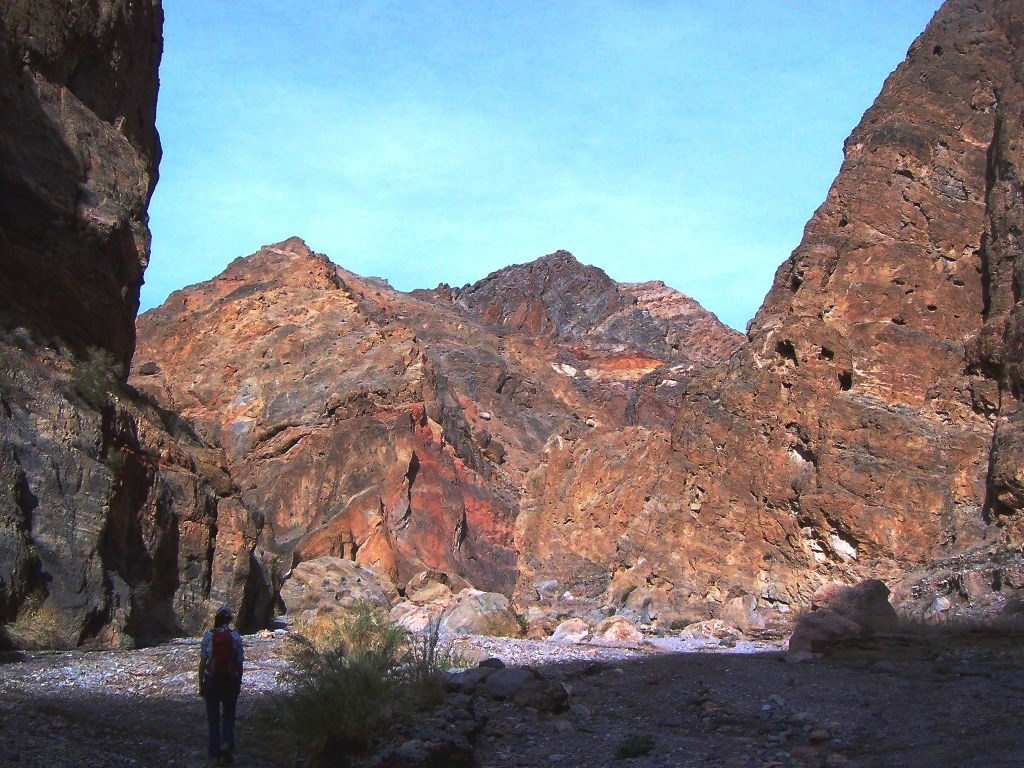 A hiker walks up canyon toward mountains