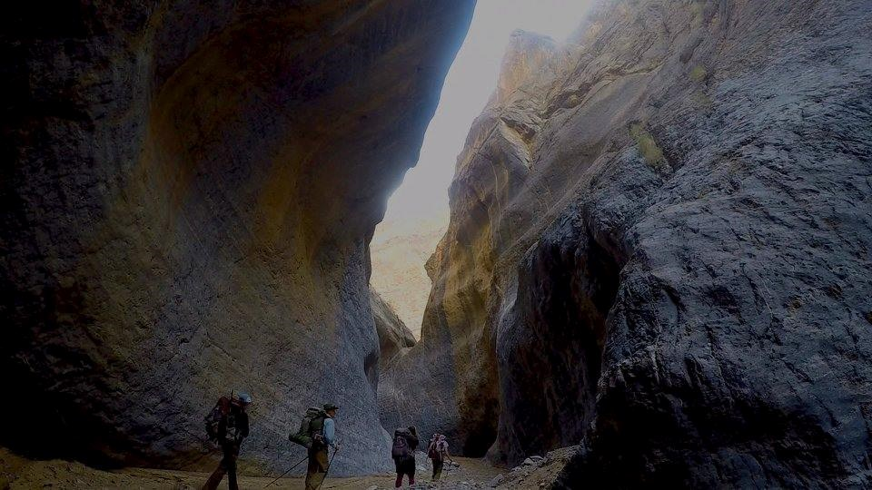 Four backpackers seem tiny as they venture between dark and polished towering canyon walls.