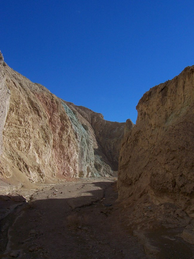 A narrow canyon with yellow, red, and green colored walls beneath a cloudy blue sky.