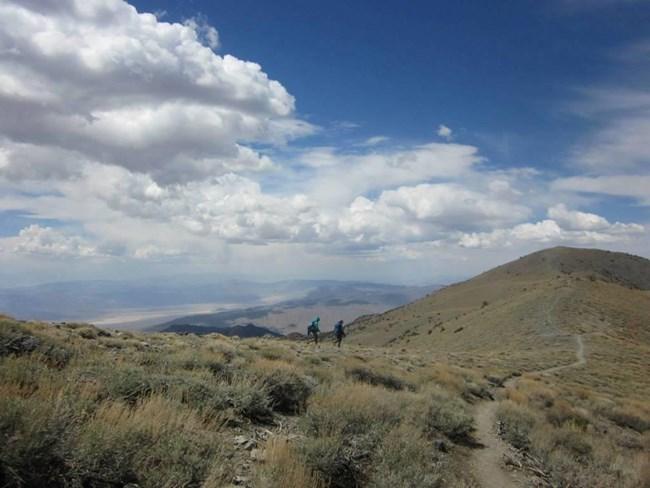 Two hikers descend to an alpine meadow from a narrow ridge.